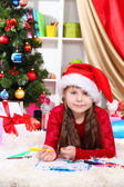 Beautiful little girl writes letter to Santa Claus in festively decorated room — Stock Photo