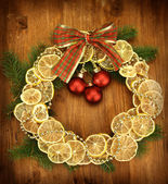 De kroon van kerstmis van gedroogde citroenen met fir tree en ballen, op houten achtergrond — Stockfoto
