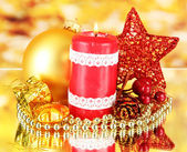 Red candle with christmas decoration on bright background — Стоковое фото