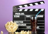 Film filmklapper, cola en popcorn op paarse achtergrond — Stockfoto