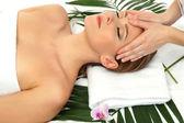 Portrait of beautiful woman in spa salon taking head massage — Stock Photo