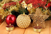 Christmas composition with candles and decorations in red and gold colors on wooden background — Стоковое фото