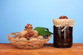 Jam-jar of walnuts on wooden table and a basket with walnuts on blue background — Foto Stock