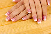 Woman hands with french manicure on wooden background — Stock Photo