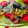 Spa stones with rose petals and candles in water on plate — Stock Photo #16930053