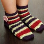 Legs female in striped socks on laminate floor — Stock Photo #16930173