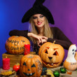 Halloween witch with pumpkins on color background — Stock Photo #16930203