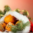 Christmas composition with oranges and fir tree in Santa Claus hat — Stock Photo #16930295