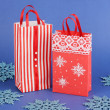 Christmas paper bags for gifts on blue background — Stock fotografie
