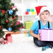 Child in Santa hat sits near Christmas tree with gift in hands — Stock Photo #16930665