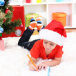 Little boy in Santa hat writes letter to Santa Claus — Stock Photo #16930671