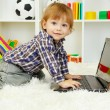Cute little boy and notebook in room — Stock Photo