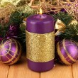 Christmas composition with candles and decorations in purple and gold colors on wooden background — Stock Photo #16931409