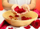 Mains de femme avec un bol en bois de l'eau avec des pétales, sur fond rouge — Photo