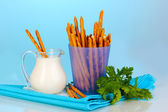 Tasty crispy sticks in purple plastic cup on blue background — Stock Photo