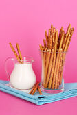 Tasty crispy sticks in glass cup on pink background — Stock Photo