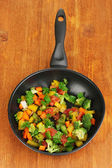 Sliced fresh vegetables in pan on wooden table — Stock Photo