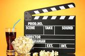 Film filmklapper, cola en popcorn op oranje achtergrond — Stockfoto