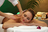 Beautiful woman in spa salon with stones getting massage, on green background — Stock Photo