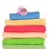 Stack of towels with fragrant flower isolated on white — Stock Photo