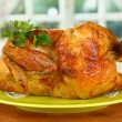 Roasted whole chicken on a green plate on wooden background close-up — Stock Photo
