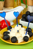Feta cheese cubes on plate with olives on wooden table close-up — Stock Photo