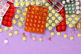 Capsules and pills packed in blisters on purple background — Stock Photo
