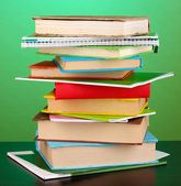 Stack of interesting books and magazines on wooden table on green background — Stock Photo