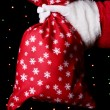 Santa Claus hand holding bag of gifts on bright background — Stock Photo #16950175