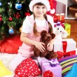 Little girl in Santa hat near the Christmas tree in festively decorated room — Stock Photo #16950399