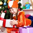 Stock Photo: Little girl in suit of squirrels opens gift in festively decorated room