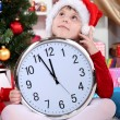 Beautiful little girl with clock in anticipation of New Year in festively decorated room — стоковое фото #16950417