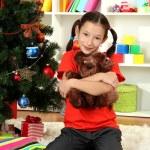 Little girl holding toy near christmas tree — Stock Photo #16950525