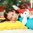 Little girl sleeping near christmas tree — Stock Photo #16950529