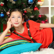 Stock Photo: Little girl dreaming near christmas tree