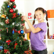 图库照片: Little girl decorating christmas tree
