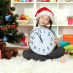 Little girl holding clock near christmas tree — Stock Photo