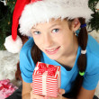 Little girl holding gift box near christmas tree — Stockfoto