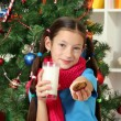 Stock Photo: Little girl with pink scarf and glass of milk sitting near christmas tree