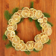 Christmas wreath of dried lemons with fir tree, on wooden background — Photo