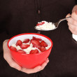 Young woman is eating cottage cheese with sliced strawberries — Stock Photo #16950803