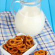 Tasty pretzels in white bowl and milk jug on wooden table close-up — Stock Photo #16950991