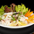 Delicatessen seafood salad with rice isolated on black — Stock Photo