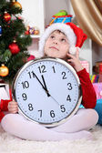 Beautiful little girl with clock in anticipation of New Year in festively decorated room — Stok fotoğraf