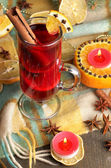 Fragrant mulled wine in glass with spices and oranges around on wooden table — Stock Photo