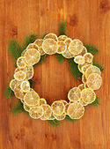 De kroon van kerstmis van gedroogde citroenen met fir tree, op houten achtergrond — Stockfoto