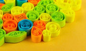Colorful quilling on yellow background close-up — Zdjęcie stockowe
