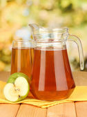 Full glass and jug of apple juice and apples on wooden table outdoor — Stock Photo