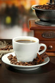 Cup of coffee, grinder and coffee beans in cafe — Stock Photo