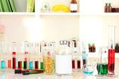 Различные лабораторная посуда с жидкость цвета на фоне лаборатории — Стоковое фото
